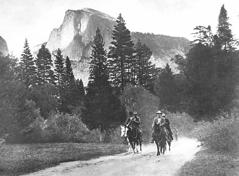 President Theodore Roosevelt and John Muir riding horses along a road in Yosemite Valley, with Half Dome in the distance, accompanied by Park Rangers Archie Leonard and Charles Leidig, followed by unidentified man on foot; left to right, Leonard, Muir, Roosevelt, Leidig
